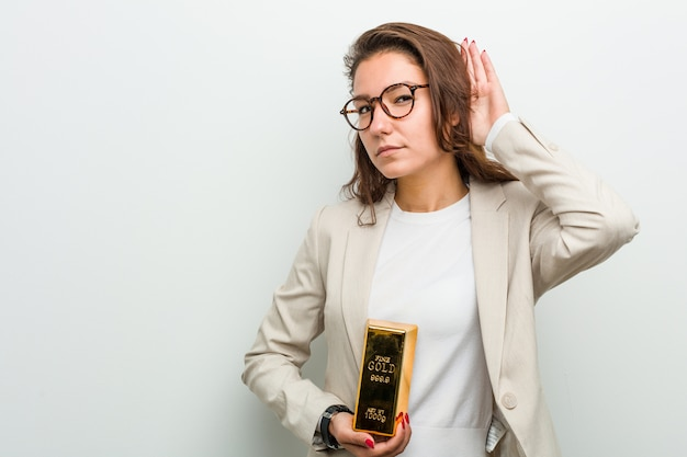 Junge europäische frau, die einen goldbarren versucht, einen klatsch zu hören hält. Premium Fotos