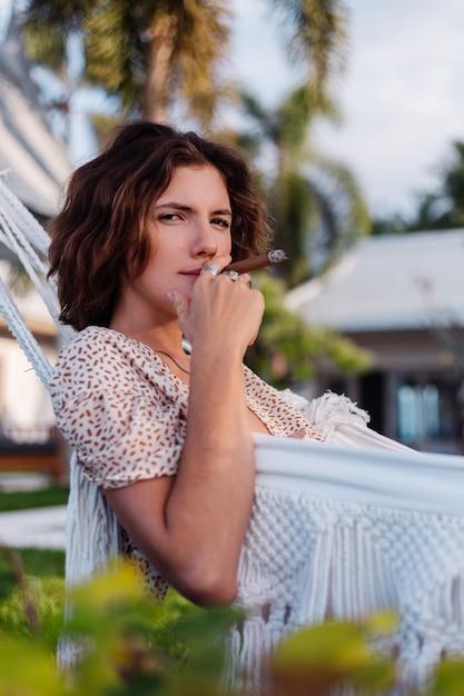 Junge europäische frau, die zigarre raucht, die auf hängematte außerhalb des tropischen luxusvillenhotels liegt, natürliches licht des sonnenuntergangs Kostenlose Fotos