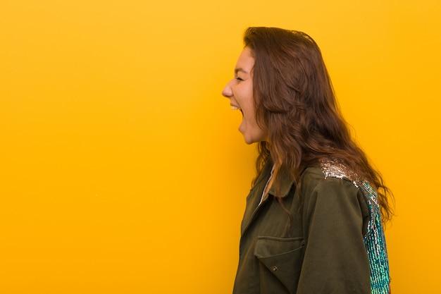 Junge europäische frau getrennt über dem gelben schreien in richtung zu einer kopie Premium Fotos