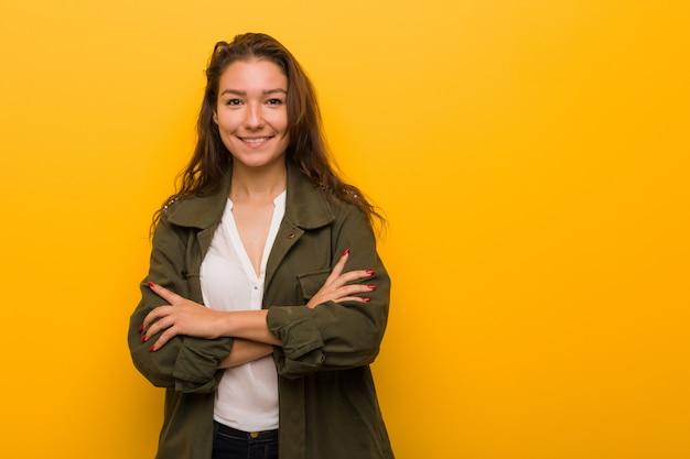Junge europäische frau lokalisiert über gelbem hintergrund, der sich überzeugt fühlt und arme mit entschlossenheit kreuzt. Premium Fotos