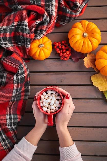 Junge europäische frau mit roter maniküre auf nägeln hält in händen rote tasse kakao mit marshmallows Premium Fotos