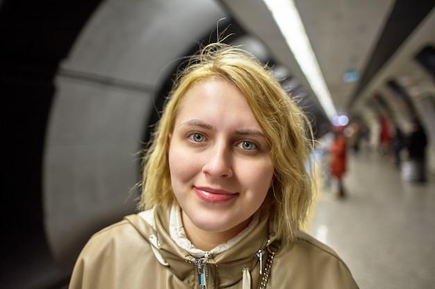 Junge europäische frau steht auf dem bahnsteig einer u-bahnstation und wartet auf zug. Premium Fotos