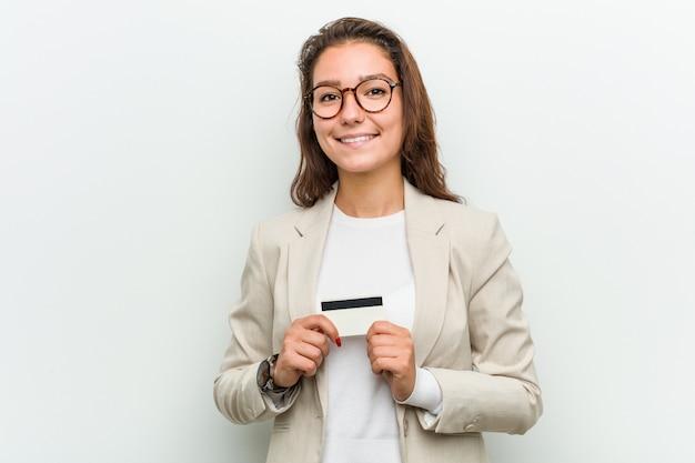 Junge europäische geschäftsfrau, die eine kreditkarte glücklich, lächelnd und nett hält. Premium Fotos