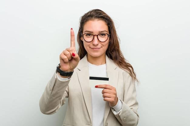 Junge europäische geschäftsfrau, die eine kreditkarte zeigt nummer eins mit dem finger hält. Premium Fotos