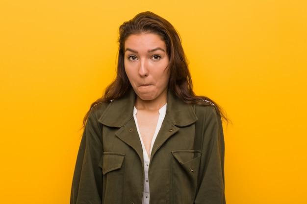 Junge europäische konfuse frau getrennt über gelbem hintergrund Premium Fotos