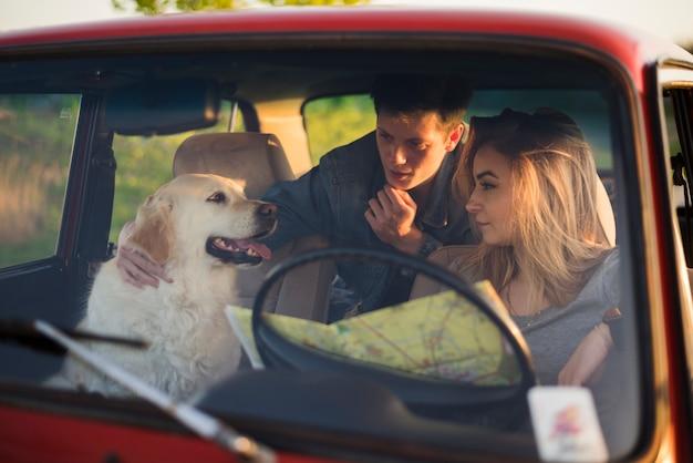Junge familie auf einer autoreise mit ihrem hund Kostenlose Fotos