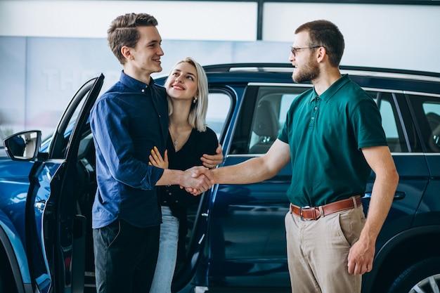 Junge familie, die ein auto in einem autosalon kauft Kostenlose Fotos