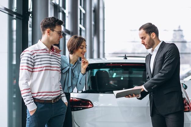 Junge familie, die ein auto kauft Kostenlose Fotos
