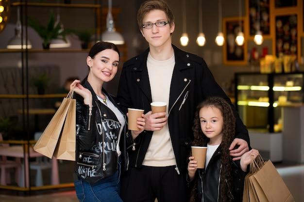 Junge familie, die zeit in einem café nach dem einkaufen hat mama papa kleine tochter tee und café trinken Premium Fotos