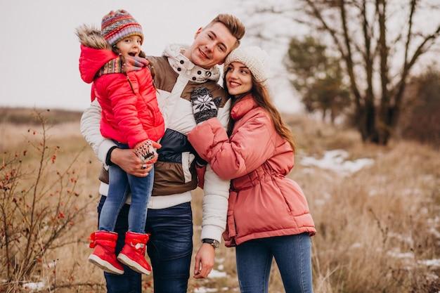 Junge familie, die zusammen in wald zur winterzeit geht Kostenlose Fotos