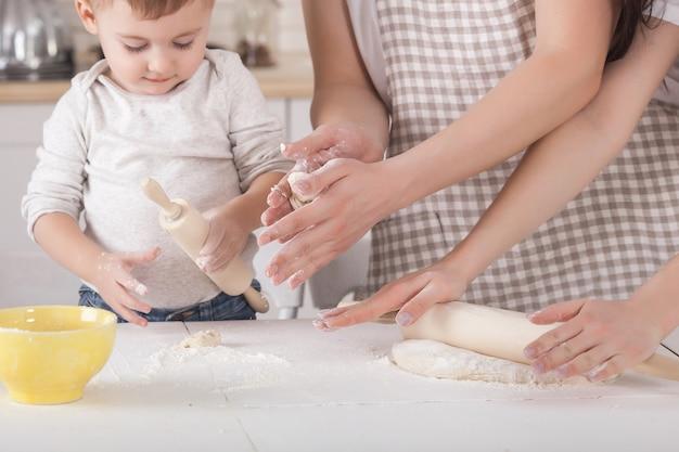 Junge familie, die zusammen kocht. ehemann, ehefrau und ihr kleines baby in der küche. familie, die den teig mit mehl knetet. die leute kochen das abendessen oder frühstück. Premium Fotos