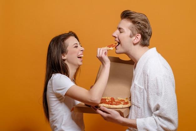Junge familie in der hauskleidung auf gelbem orange in der quarantäne mit italienischen pizza-peperoni füttern einander gute familienbeziehungen lustiges familienkonzept Premium Fotos