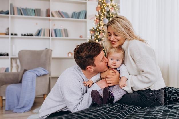 Junge familie mit dem baby, das durch weihnachtsbaum sitzt Kostenlose Fotos