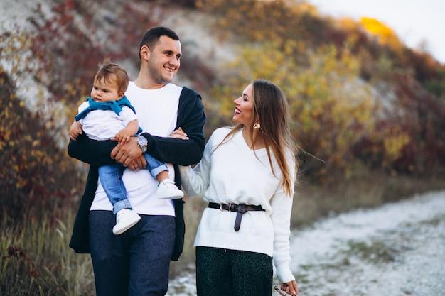 Junge familie mit dem kleinen sohn, der im park geht Kostenlose Fotos