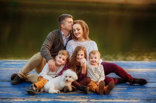 Junge familie mit drei kindern und einem hund auf einem spaziergang im herbstlichen wald Premium Fotos