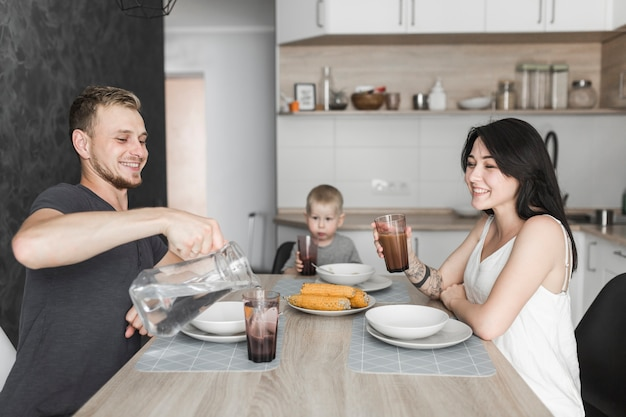 Junge familie mit ihrem kleinkindsohn, der in der küche frühstückt Kostenlose Fotos
