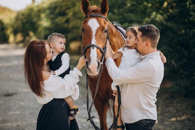 Junge familie mit kindern, die spaß mit pferd im wald haben Kostenlose Fotos
