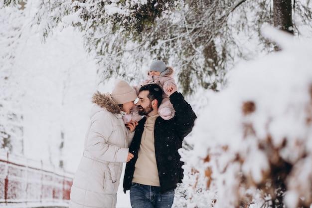 Junge familie mit kleiner tochter in einem winterwald voll des schnees Kostenlose Fotos