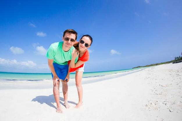 Junge familie von zwei am weißen strand haben viel spaß Premium Fotos