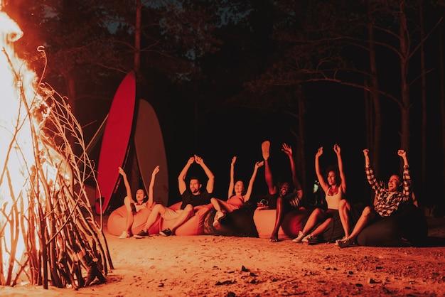 Junge firma sitzen vor lagerfeuer am strand. Premium Fotos