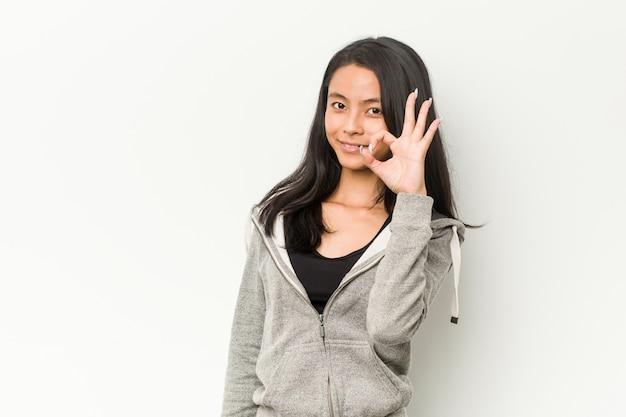 Junge fitness asiatische frau fröhlich und zuversichtlich zeigt ok geste Premium Fotos