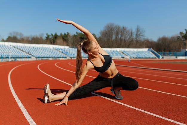 Junge fitness-frauenläufer wärmen sich auf, bevor sie auf spur laufen. morgenübungen im sommer Premium Fotos