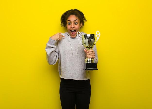 Junge fitness schwarze frau überrascht, fühlt sich erfolgreich und wohlhabend. eine trophäe in der hand. Premium Fotos
