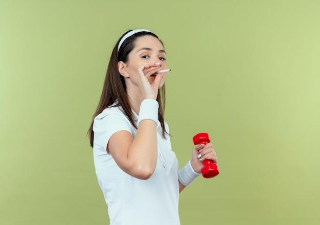 Junge fitnessfrau im stirnband, das mit hantel arbeitet und eine zigarette raucht, die über lichtwand steht Kostenlose Fotos