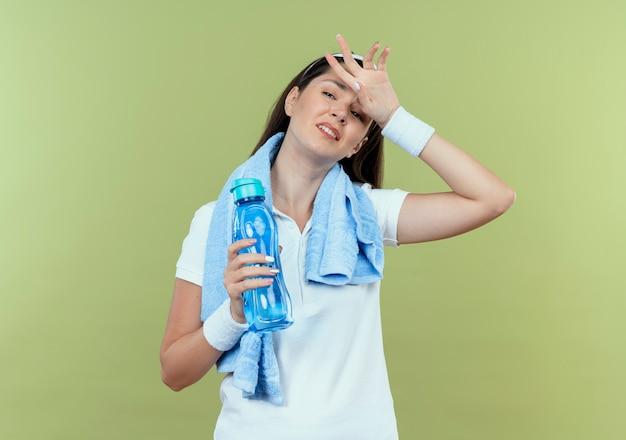 Junge fitnessfrau im stirnband mit handtuch um den hals, der flasche wasser hält, die müde und erschöpft nach dem training steht, das über lichtwand steht Kostenlose Fotos