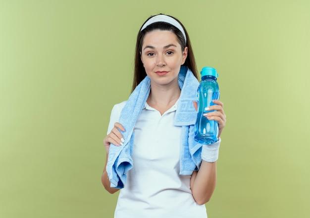 Junge fitnessfrau im stirnband mit handtuch um den hals hält flasche wasser lächelnd zuversichtlich über heller wand stehend Kostenlose Fotos