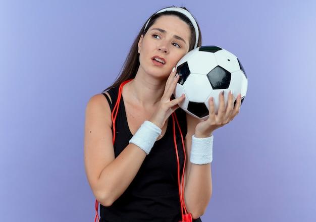 Junge fitnessfrau im stirnband mit springseil um den hals, der fußball hält, der reifen und gelangweilt steht, die über blaue wand stehen Kostenlose Fotos