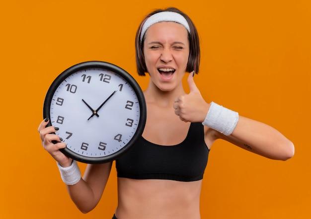Junge fitnessfrau in sportbekleidung mit stirnband, das wanduhr glücklich und aufgeregt zeigt daumen hoch stehend über orange wand Kostenlose Fotos