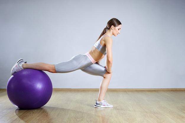 Junge fitte frau, die in einem fitnessstudio trainiert. sportmädchen trainiert cross fitness mit pilates balls. Premium Fotos