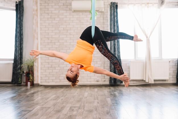 Junge flexible gesunde frau, die luftyoga in der turnhalle tut Kostenlose Fotos