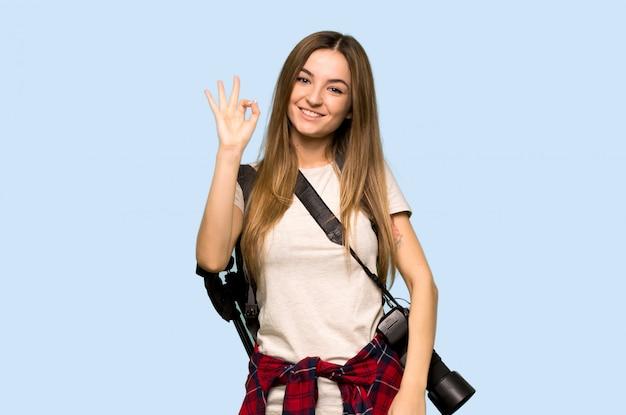Junge fotograffrau, die ein okayzeichen mit den fingern auf lokalisiertem blauem hintergrund zeigt Premium Fotos