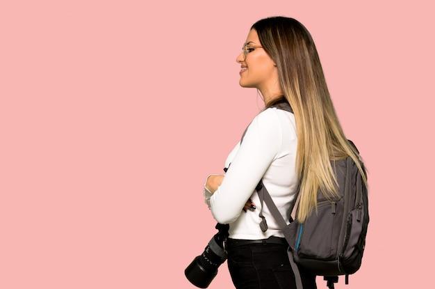 Junge fotograffrau in seitlicher position auf lokalisierter rosa wand Premium Fotos