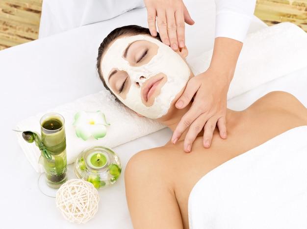 Junge frau am spa-salon mit kosmetischer maske auf gesicht. high angle foto Kostenlose Fotos