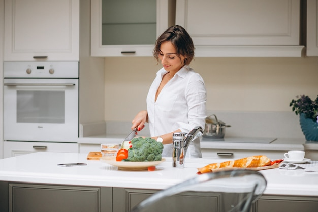 Junge frau an der küche frühstück kochend Kostenlose Fotos
