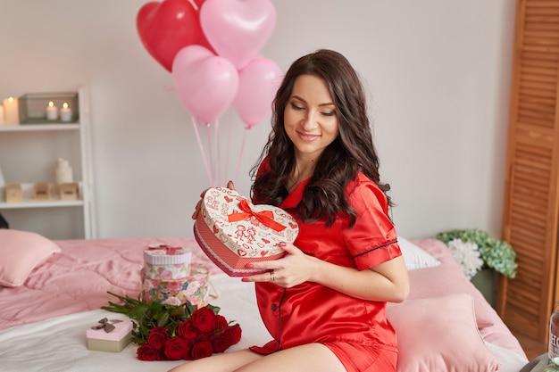 Junge frau auf bett im roten pyjama mit herzförmiger geschenkbox Premium Fotos