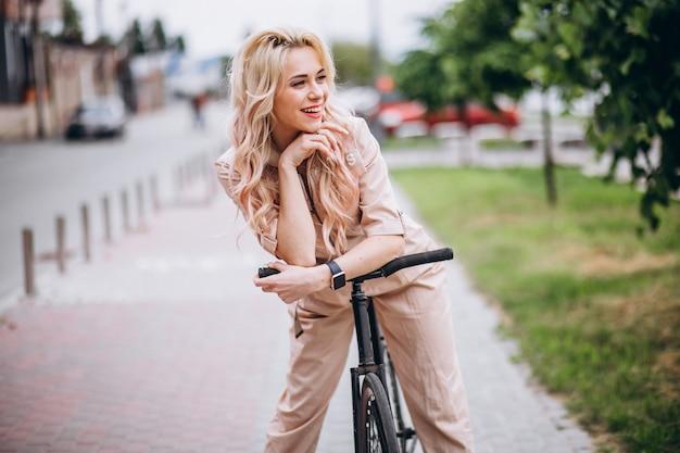 Junge frau auf einem fahrrad im park Kostenlose Fotos