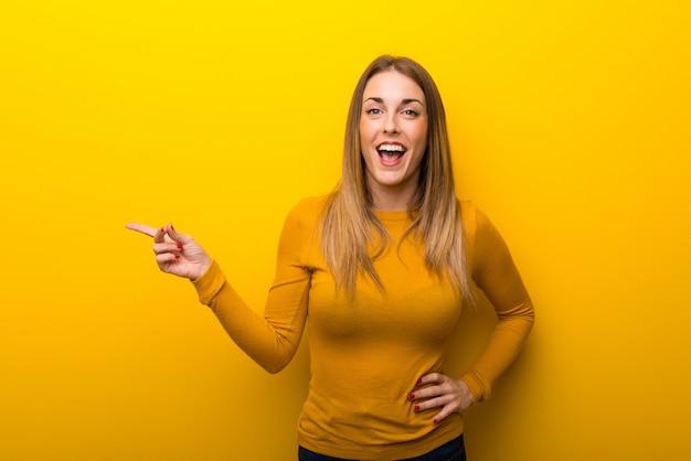 Junge frau auf gelbem hintergrund finger auf die seite zeigend und ein produkt darstellend Premium Fotos