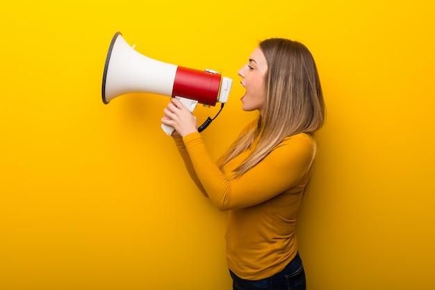 Junge frau auf gelbem hintergrund schreit durch ein megaphon, um etwas in seitlicher position anzukündigen Premium Fotos