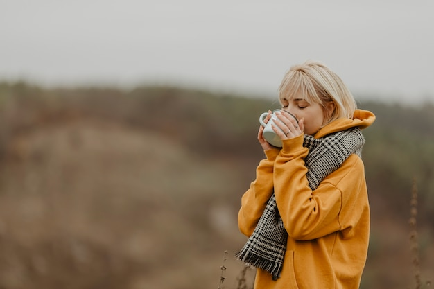 Junge frau auf trinkendem tee der winterreise Kostenlose Fotos