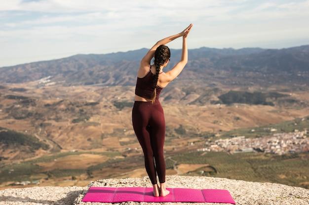 Junge frau auf übendem yoga des berges Kostenlose Fotos