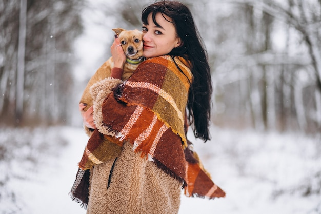 Junge frau außerhalb des parks mit ihrem kleinen hund am winter Kostenlose Fotos