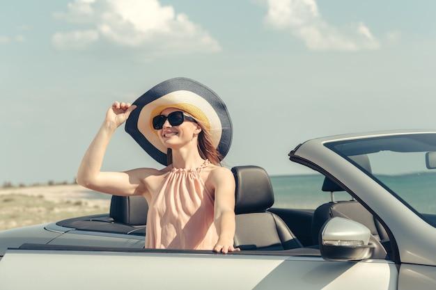 Junge frau autofahren am strand Premium Fotos