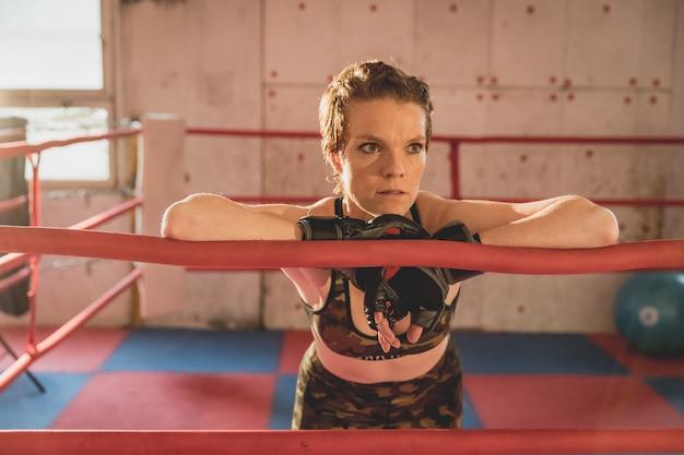 Junge frau bereitet sich auf streichhölzer mma im käfig vor. training in einer sporthalle Premium Fotos