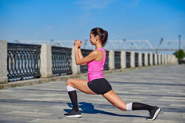 Junge frau der eignung, die beine nach lauf ausdehnt. draußen sport porträt Premium Fotos