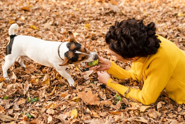 Junge frau der nahaufnahme, die mit ihrem hund spielt Kostenlose Fotos