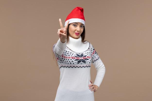 Junge frau der vorderansicht, die nummer auf weihnachtsemotion des braunen hintergrundfeiertags zeigt Kostenlose Fotos